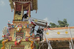 20 metres in the air, the coffin is carefully passed from hand to hand