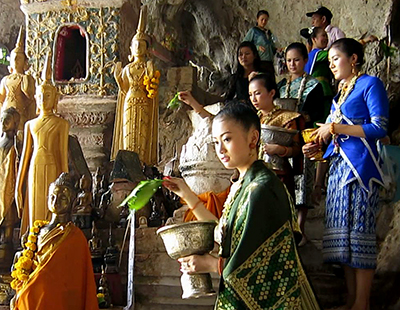 The daughters of Ka Bin La Phom sprinkling holy water on Buddhas at Pac Ou Caves