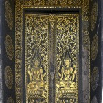 Gold stencils on black background decorate entry doors to Wat That Luang, Luang Prabang, Laos